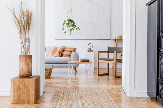 The modenr boho interior of living room in cozy apartment with design coffee table, gray sofa, wooden cube honey yellow pillow, desk, green armchair, plants and elegant accessories. Modern home decor.