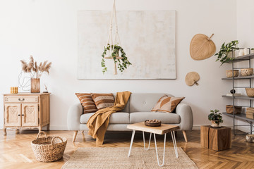 The stylish boho compostion at living room interior with design gray sofa, wooden coffee table, commode and elegant personal accessories. Honey yellow pillow and plaid. Cozy apartment. Home decor Fototapete