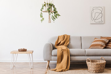 Modern boho interior of living room at cozy apartment with gray sofa, honey yellow pillows and plaid, plants, paintings, rattan basket and design personal accessories. Stylish home decor. Template. Wall mural