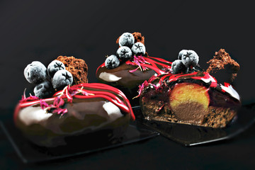 Sliced red and black chocolate dessert with frozen aronia berries and orange and chocolate insertion