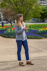 Young woman standing holding her phone in a park.