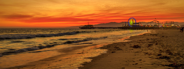Foto op Plexiglas Rood Amazing landscape of iconic Santa Monica Pier at orange red sunset sky from beach on Paficif Ocean. Santa Monica Historic Landmark, California, USA. Wide banner panorama.