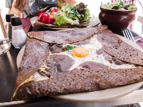 The close up image of Galette. Galette is frequently garnished with egg, meat, fish, cheese, cut vegetables, apple slices, berries, or similar ingredients.