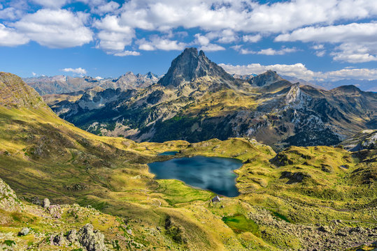 View at Ossau valley from the mountain pass Ayous in Franch Atlantic Pyrenees, as seen in October. Lake Gentau is at foreground of the famous Pyrenean peak Midi Ossau.