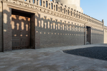 Stone bricks old decorated fence with wooden doors and shadows of decorations of the opposite fence, Mosque of Ibn Tulun, Old Cairo, Egypt