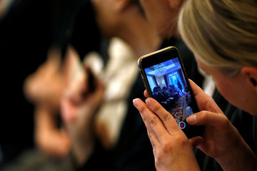 A woman takes a picture with her phone as models present creations by designer Ralph Rucci as part of his Haute Couture Fall/Winter 2019/20 collection show for RR331 in Paris
