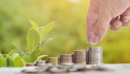 Businessman hand putting coins stack on table with blur nature bokeh background in park. Concept financial saving success growing investment.