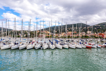 Sailboats neatly in a row in the harbour and houses on the hills, against cloudy sky in Lerici in Liguria, Italy