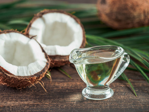 Liquid coconut MCT oil and halved coco-nut on wooden table. Health Benefits of MCT Oil. MCT or medium-chain triglycerides, form of saturated fatty acid.