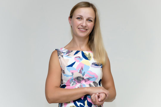 Portrait of a pretty beautiful adult female 35 years old blonde on a white background in a light dress with a pattern. Standing in front of the camera, smiling.