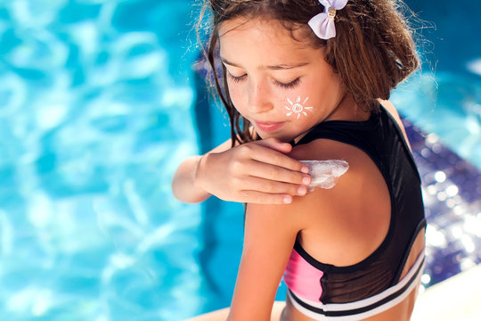 Kid girl applies sun protection cream on the skin. Children, summer, holiday and healthcare concept
