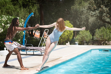 black guy with dreadlocks playing in a pool with caucasian girl.