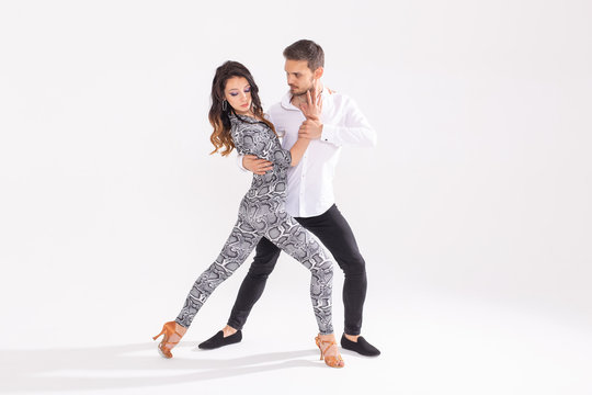 Social dance concept - Active happy adults dancing bachata or salsa together over white background with copy space