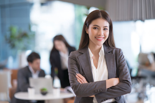 Portrait of successful young Asian businesswomanat office, colleagues in background.