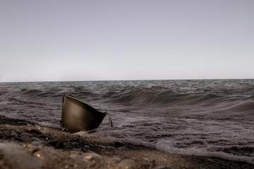 vintage photo of military helmet on beach waves pushing helmet onto shore