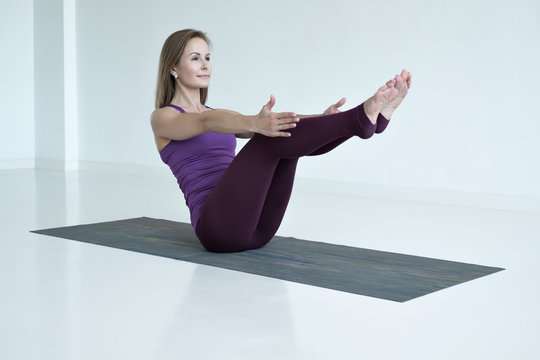 Caucasian slim woman practicing yoga, doing Paripurna Navasana exercise, boat pose. Indoor full length in white studio
