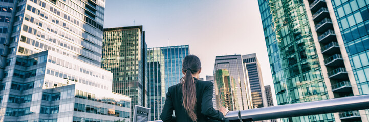 Business woman in city center looking at view of skyline skyscrapers in Vancouver downtown , Canada. Businesswoman from the back contemplating career and job. Banner panorama.