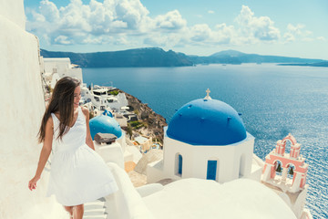 Wall Mural - Santorini travel tourist woman on vacation in Oia walking on stairs. Asian girl in white dress visiting the famous white village with the mediterranean sea and blue domes. Europe summer destination.