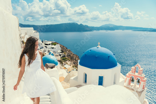 Wall mural Santorini travel tourist woman on vacation in Oia walking on stairs. Asian girl in white dress visiting the famous white village with the mediterranean sea and blue domes. Europe summer destination.
