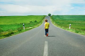 A boy walks down the street in the field