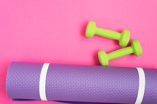 Yoga mat and dumbbells over pink background, top view. Sport concept