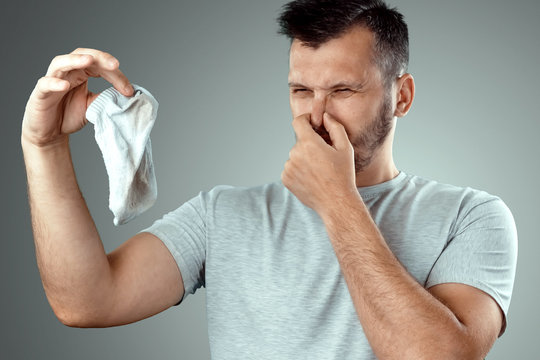 A young man holds his smelly socks and covers his nose with his hand. Nasty smell. Stink legs, fungus on the legs