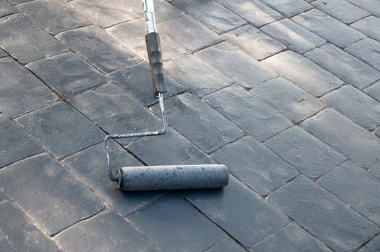 Sealing and painting a gray concrete cobblestone-like driveway with a roller tool.