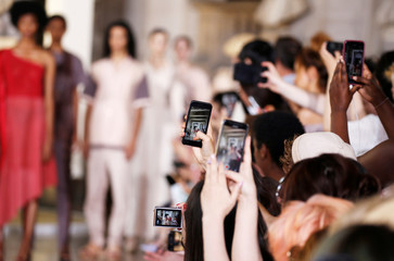 People take pictures as models present creations by designer Yuima Nakazato as part of his Haute Couture Fall/Winter 2019/20 collection show in Pari
