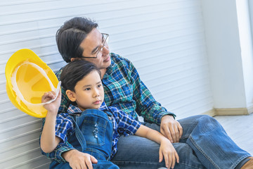 Builder father is sitting next to his son for family connection concept.