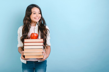 Portrait of smiling nerd young girl holding stack of books with apple on it. Back to school. - Copyspace
