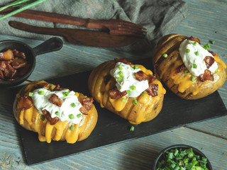 Fototapete - baked potato stuffed with cheese, bacon and sour cream loaded hasselback potatoes