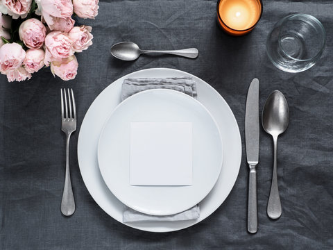 Menu, wedding invitation mock up. Beautiful table setting on gray linen tablecloth. Festive table setting for wedding dinner with pink spray roses and cabdle. Holiday dinner, white plates. Copy space