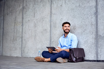 Smilling young businessman in wireless headphones sitting with tablet and looking away