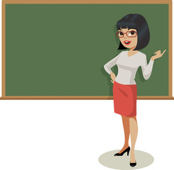 Young female teacher gestures in front of a traditional blackboard.