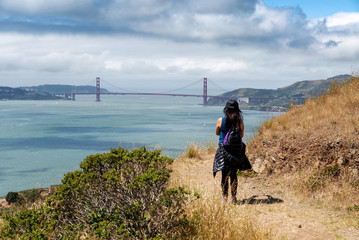 Hiker on trail to Mt. Livermore on Angel Island in San Francisco Bay with Golden Gate Bridge in background