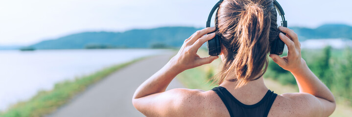 Young teenager girl adjusting  wireless headphones before starting jogging and listening to music. Web page header cropping. Wall mural