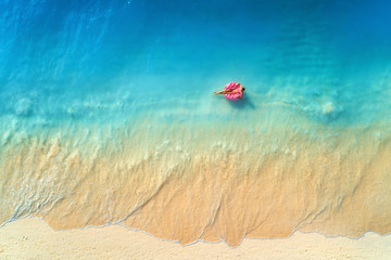 Aerial view of a young woman swimming with the donut swim ring in the clear blue sea with waves at sunset in summer. Tropical aerial landscape with girl, azure water, sandy beach. Top view. Travel Fototapete
