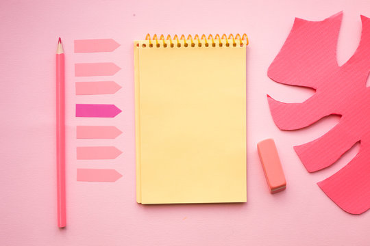 Blank page of vertical spiral note pad with crayon, eraser and artificial leaf on pink background