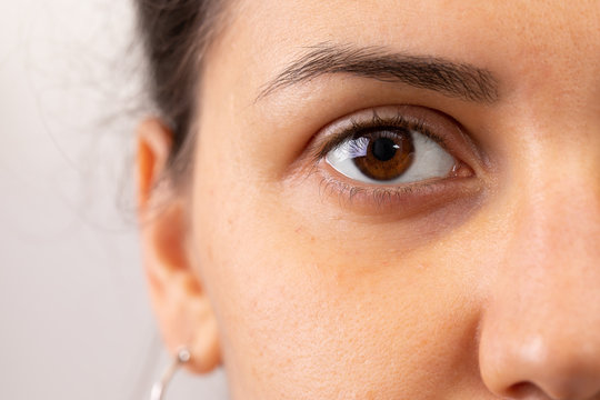 A closeup view on the eye of a beautiful young woman. A slight dark circle can be seen beneath the eye. Details of girl with brown iris. Copy space on the left.