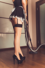 sexy maid in stockings using vacuum cleaner. attractive woman in lingerie. adult role play games