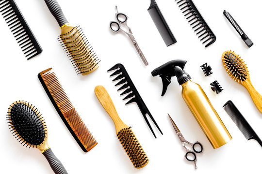Combs, sciccors and hairdresser tools in beauty salon work desk on white background top view pattern