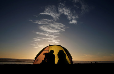A man take a picture inside of his tent during the sunset in a beach at La Serena