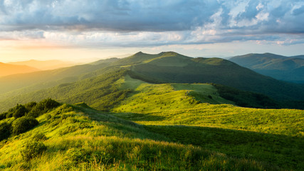 Stunning summer sunrise in the mountains. Beautiful green alpine meadow and blue sky. Polonina Wetlinska. Bieszczady. Poland Fototapete