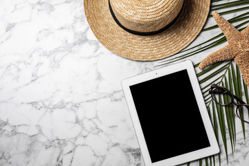 Flat lay composition with tablet and travel blogger's stuff on marble background, space for text