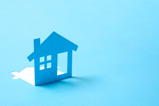 Concept of house in paper on blue color background for real estate property industry