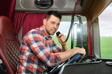Driver using CB radio in cab of modern truck