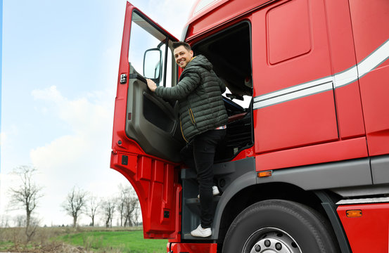 Portrait of happy driver getting into cab of modern truck
