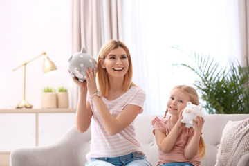 Mother and daughter with piggy banks at home