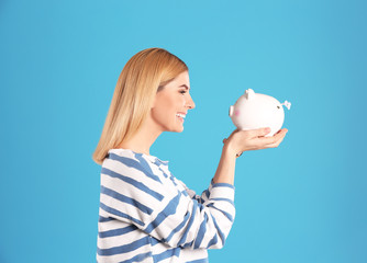 Woman with piggy bank on color background