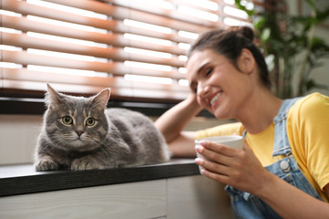 Young woman with cute cat at home. Pet and owner